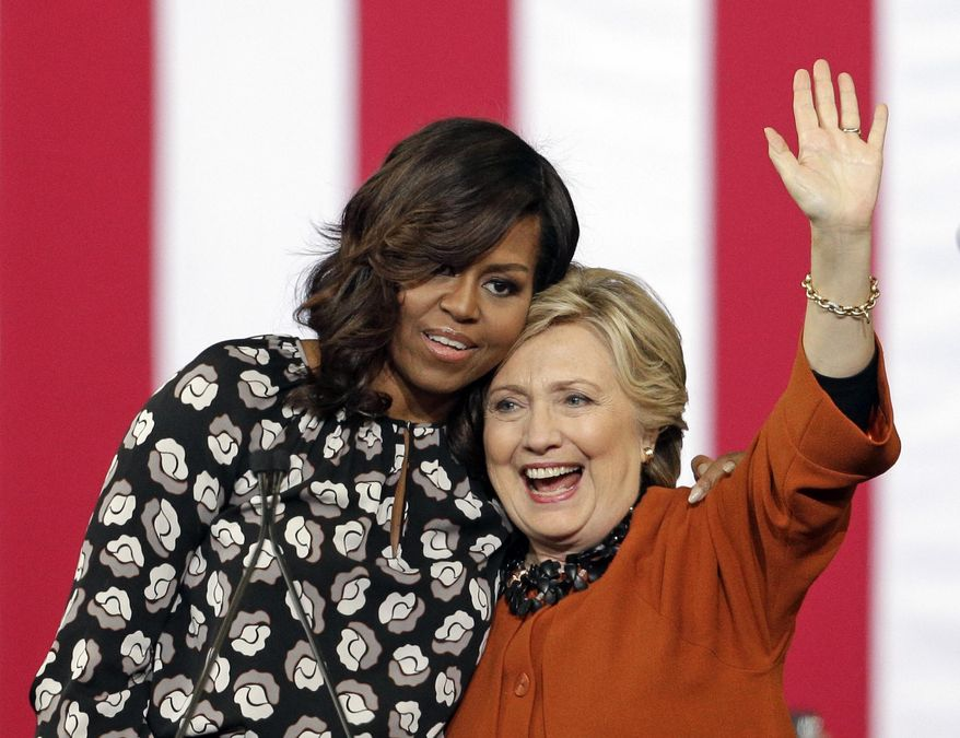 FILE - In this Oct. 27, 2016, file photo, Democratic presidential candidate Hillary Clinton is hugged by first lady Michelle Obama during a campaign rally in Winston-Salem, N.C. When Michelle Obama considered the daunting prospect of becoming first lady, she purposely avoided turning to books by her predecessors for guidance. Instead, she turned inward.  (AP Photo/Chuck Burton, File)