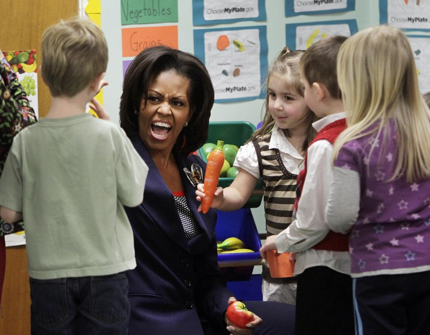 FILE - In this March 9, 2012, file photo, first lady Michelle Obama gives a high five during a stop with pre-schoolers at the Penacook Community Centervin Concord, N.H., as part of her Let's Move initiative. When Michelle Obama considered the daunting prospect of becoming first lady, she purposely avoided turning to books by her predecessors for guidance. Instead, she turned inward.(AP Photo/Jim Cole, File)