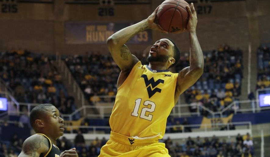 West Virginia guard Tarik Phillip (12) drives to the basket while being defended by Northern Kentucky guard Lavone Holland II (30) during the second half of an NCAA college basketball game, Friday, Dec. 23, 2016, in Morgantown, W.Va. (AP Photo/Raymond Thompson)