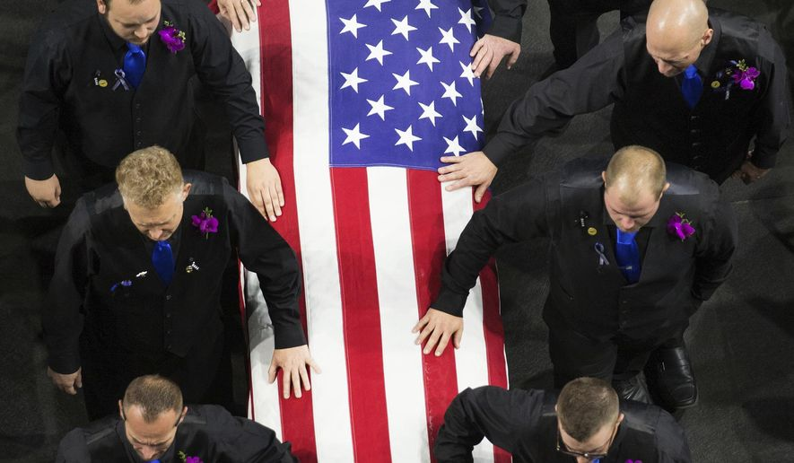 FILE - This Nov. 14, 2016, file photo, pallbearers walk with the casket of West Valley City Police officer Cody Brotherson as they enter for funeral services at the Maverik Center in West Valley City, Utah. Three Utah teenagers have been charged with murder and theft after a police officer was killed during a chase of a stolen car, according to court documents released Friday, Dec. 23, following a push by media outlets. (Scott G Winterton/The Deseret News via AP, File)