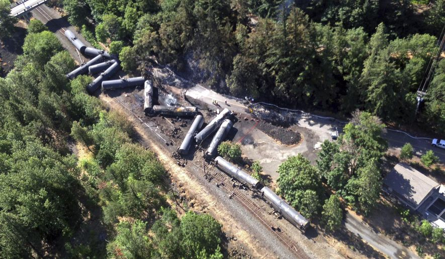 FILE - This June 4, 2016, file aerial photo, provided by the Washington State Department of Ecology, shows scattered and burned oil tank cars after a train derailed and burned near Mosier, Ore. The nation's largest railroad has agreed to more thorough inspections and maintenance improvements after the fiery oil train derailment in Oregon and the discovery of more than 800 potential safety violations across its sprawling network. (Washington State Dept. of Ecology via AP, file)