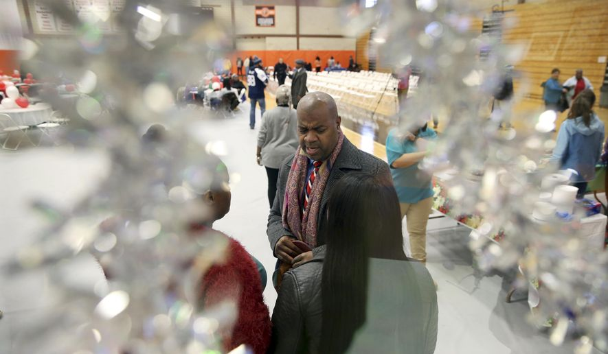 Newark Mayor Ras Baraka, center, is seen through Christmas decorations as he greets people at a Newark's Weequahic High School high school at an event to feed residents as part of a program to bring holiday cheer Friday, Dec. 23, 2016, in Newark, N.J. London-born actor Delroy Lindo joined Baraka. (AP Photo/Mel Evans)