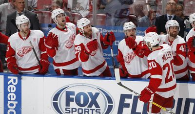 Detroit Red Wings left wing Drew Miller (20) is congratulated by teammates after scoring a goal against the Florida Panthers during the third period of an NHL hockey game, Friday, Dec. 23, 2016, in Sunrise, Fla. (AP Photo/Joel Auerbach)