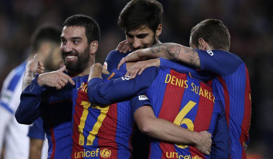 FC Barcelona's Paco Alcacer, left, is congratulated by his teammates after scoring a goal during the Copa del Rey, Spain's King's Cup soccer match between FC Barcelona and Hercules at the Camp Nou in Barcelona, Spain, Wednesday, Dec. 21, 2016. (AP Photo/Manu Fernandez)