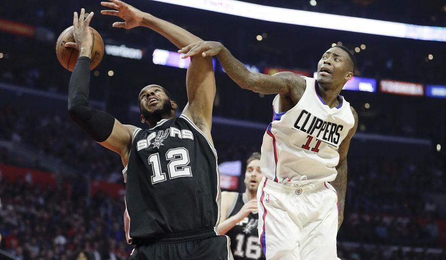 San Antonio Spurs' LaMarcus Aldridge, left, is fouled by Los Angeles Clippers' Jamal Crawford during the first half of an NBA basketball game Thursday, Dec. 22, 2016, in Los Angeles. (AP Photo/Jae C. Hong)