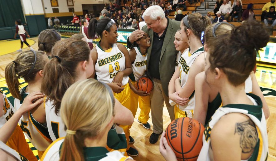 In this Tuesday, Dec. 13, 2016 photo, West Virginia Gov.-elect, Jim Justice, center, hugs guard Kiara Smith, center left, as he talks to his team prior to the start of a girls high school basketball game in Lewisburg, W.Va. In a rarity for a sitting governor,  Justice vows to keep coaching the boy's and girl's teams after he is inaugurated on Jan. 16. (AP Photo/Steve Helber)