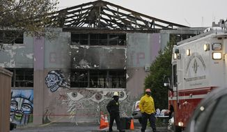 FILE - In this Dec. 7, 2016 file photo, Oakland fire officials walk past the remains of the Ghost Ship warehouse damaged from a deadly fire in Oakland, Calif. The landlord of an Oakland warehouse where 36 people died in a fire earlier this month has retained a Southern California-based attorney. Attorney Keith G. Bremer of Bremer Whyte Brown & O'Meara will represent Chor Ng, who owns the Ghost Ship property in East Oakland. (AP Photo/Eric Risberg, file)