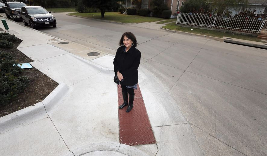 In this Friday, Dec. 9, 2016, photo, Eva Bonilla poses for a photo on a curb ramp newly built in her neighborhood in Fort Worth, Texas. The onramp to the sidewalk was built in part due to Bonilla's effort to make her community more age friendly. (AP Photo/Tony Gutierrez)