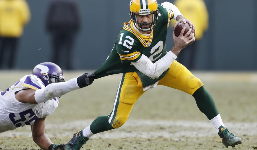 Green Bay Packers' Aaron Rodgers tries to get out of the grasp of Minnesota Vikings' Anthony Barr during the second half of an NFL football game Saturday, Dec. 24, 2016, in Green Bay, Wis. (AP Photo/Matt Ludtke)