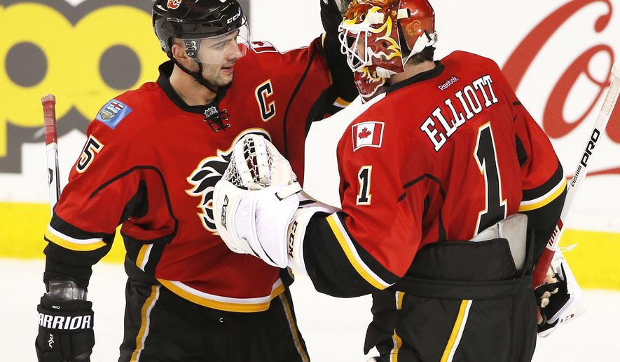 Calgary Flames' Mark Giordano, left, congratulates goalie Brian Elliott victory over the Vancouver Canucks after of an NHL hockey game in Calgary, Alberta, Friday, Dec. 23, 2016. (Larry MacDougal/The Canadian Press via AP)
