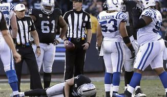Oakland Raiders quarterback Derek Carr, bottom, remains on the field after being tackled by Indianapolis Colts inside linebacker Edwin Jackson during the second half of an NFL football game in Oakland, Calif., Saturday, Dec. 24, 2016. (AP Photo/Marcio Jose Sanchez)