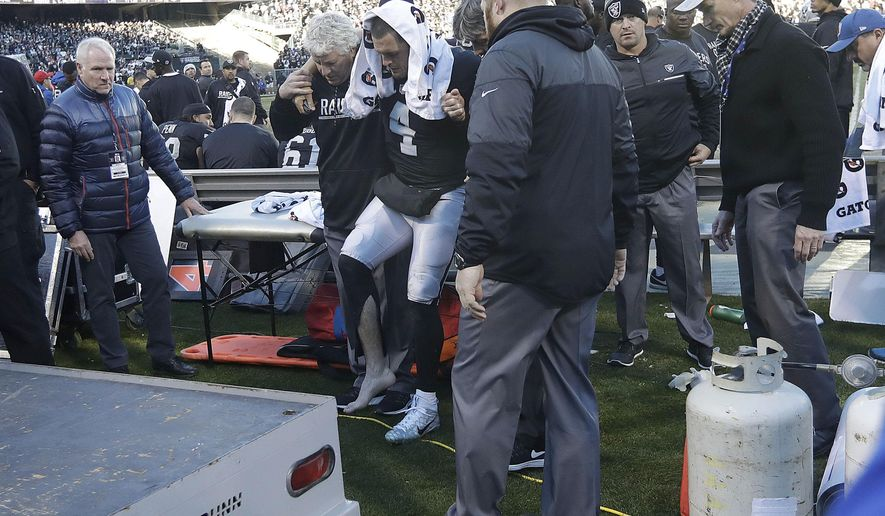 Oakland Raiders quarterback Derek Carr (4) is helped to a cart during the second half of an NFL football game against the Indianapolis Colts in Oakland, Calif., Saturday, Dec. 24, 2016. (AP Photo/Marcio Jose Sanchez)