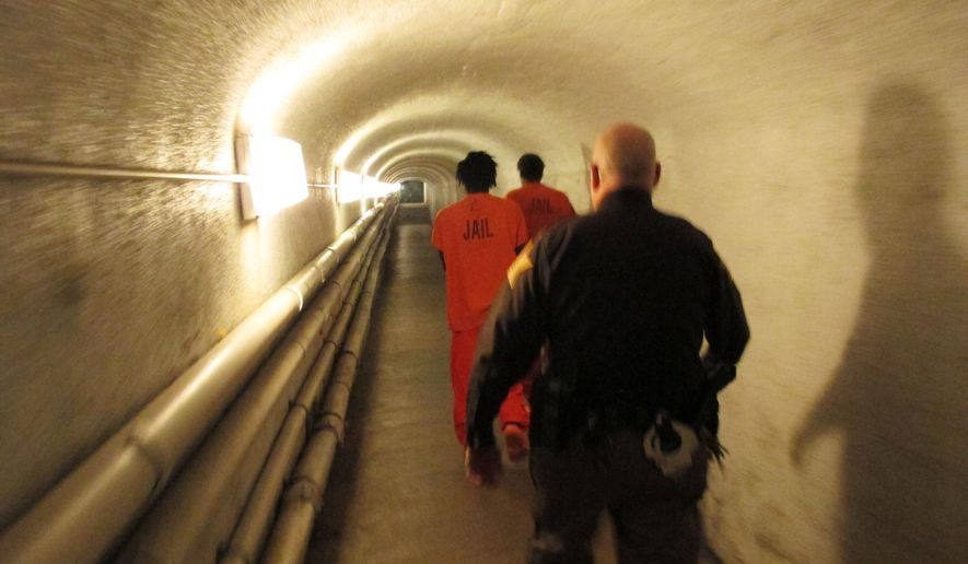 In this Thursday, Dec. 22, 2016 photo, a deputy with the Marion County Sheriff's Department leads inmates to a holding area for transfer back to the county jail in downtown Indianapolis following their court appearances. Between 30 percent and 40 percent of the jail's inmates are classified as mentally ill. Indianapolis Mayor Joe Hogsett is proposing a series of criminal justice changes aimed at making Indiana's capital the latest U.S. city to begin steering mentally ill and drug-addicted suspects into treatment instead of incarceration. (AP Photo/Rick Callahan)