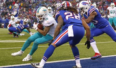 Miami Dolphins wide receiver Kenny Stills (10) scores a touchdown in front of Buffalo Bills' Ronald Darby (28) as quarterback Matt Moore (8) watches him during the second half of an NFL football game, Saturday, Dec. 24, 2016, in Orchard Park, N.Y. (AP Photo/Bill Wippert)