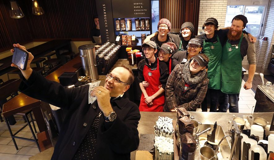In this Dec. 19, 2016 photo, Father Jim Sichko takes a selfie with employees after giving them each a $100 bill at Starbucks, in Lexington, Ky. Sichko paid out about $6,000 in holiday good will to a Starbucks counter crew, a Muslim refugee family, a Hispanic family with a desperately ill father and an LGBT man who needed help with groceries for himself and his mother. (Charles Bertram/Lexington Herald-Leader via AP)
