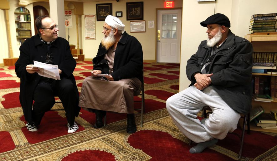 In this Dec. 19, 2016 photo, Father Jim Sichko, left, talked with Imam Mahmoud Shalash, center, and Majeed Karati, right, while explaining at the Islamic Center of Lexington, in Lexington, Ky. Sichko paid out about $6,000 in holiday good will to a Starbucks counter crew, a Muslim refugee family, a Hispanic family with a desperately ill father and an LGBT man who needed help with groceries for himself and his mother. (Charles Bertram/Lexington Herald-Leader via AP)