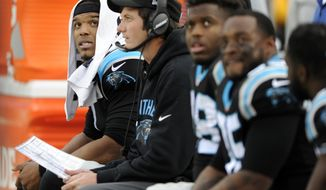 Carolina Panthers' Cam Newton, left, and others watch from the bench late in the second half of an NFL football game against the Atlanta Falcons in Charlotte, N.C., Saturday, Dec. 24, 2016. (AP Photo/Mike McCarn)