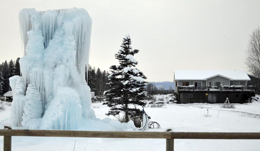 This Thursday, Dec. 15, 2016 photo shows the Olsen family's ice castle, a sculpture they created using a 1989 Ford F-150 truck, Christmas lights and a sprinkler system. The sculpture, which lights up at night, is partially an homage to Russ Olsen's father who used to build smaller structures at his home, right next for to where the Olsens live now, on the third-generation Olsen farm. Russ's father died in 1996. (Seaborn Larson/The Daily Inter Lake via AP)