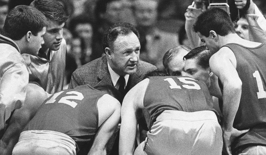 "FILE - In this Dec, 6, 1985, file photo actor Gene Hackman gives fictional Hickory High basketball players instructions during filming of the final game of the movie ""Hoosiers"" at Hinkle Fieldhouse on the Butler University campus in Indianapolis. Thirty years after the movie came out and six decades after Milan shocked the world with a 32-30 come-from-behind win over Muncie Central, the legacy of that team and those players has lasted longer than anyone could have imagined in 1954. (AP Photo/Tom Strickland, file)"