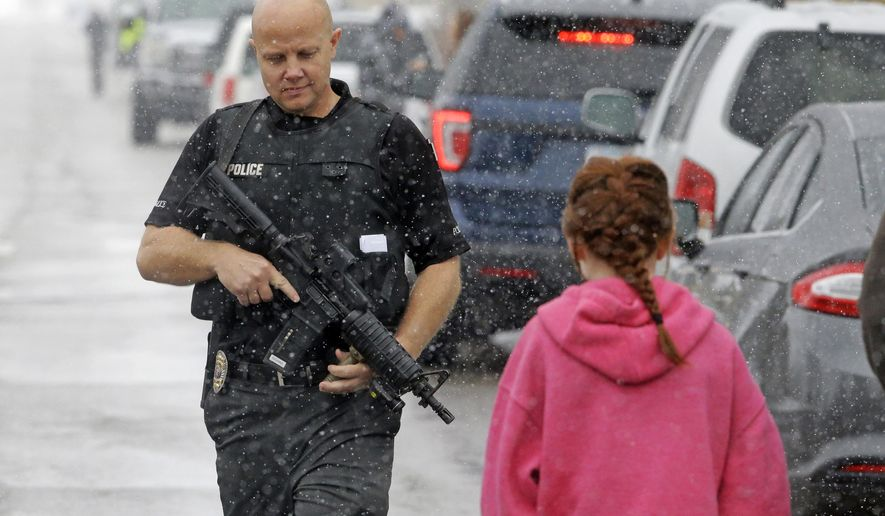 FILE - This Dec. 1, 2016, file photo, a police officer carries his weapon as he walks along the street in front of Mueller Park Junior High after a student fired a gun into the ceiling, in Bountiful, Utah. Police said a 15-year-old brought two guns to school and fired a round into a classroom ceiling before his parents arrived and disarmed him, likely preventing bloodshed. A series of violent crimes involving teenage suspects over the last two months is raising tough questions for Utah courts, police and parents. (AP Photo/Rick Bowmer, File)
