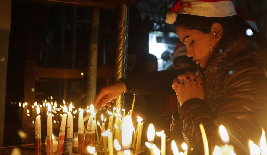A Christian worshipper prays after lighting a candle on Christmas Eve at the Church of the Nativity, built atop the site where Christians believe Jesus Christ was born, in the West Bank City of Bethlehem, Saturday, Dec. 24, 2016. (AP Photo/Majdi Mohammed)