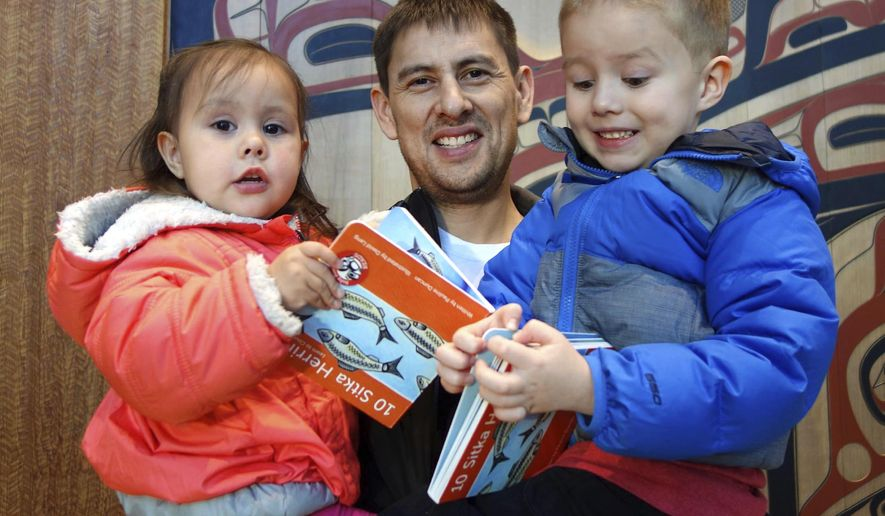"""In this Dec. 10, 2016 photo, Jeff Ketah holds his children, Selena, 2, and Dexter, 5, as they open their books, """"10 Sitka Herring"""" in Juneau, Alaska.  A Sealaska Heritage Institute program is helping to reverse a lack of children's books with an authentic focus on Alaska Native stories and culture. (Mary Catharine Martin/Capital City Weekly via AP)"""