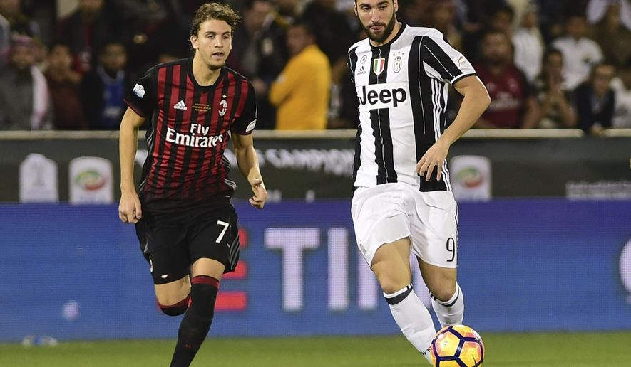Juventus's Gonzalo Higuain, right, gets the ball past AC Milan's Manuel Locatelli during the Italian Super Cup soccer match between Juventus and AC Milan, at the Al Sadd Sports Club in Doha, Qatar, Friday, Dec. 23, 2016. (AP Photo/Alexandra Panagiotidou)
