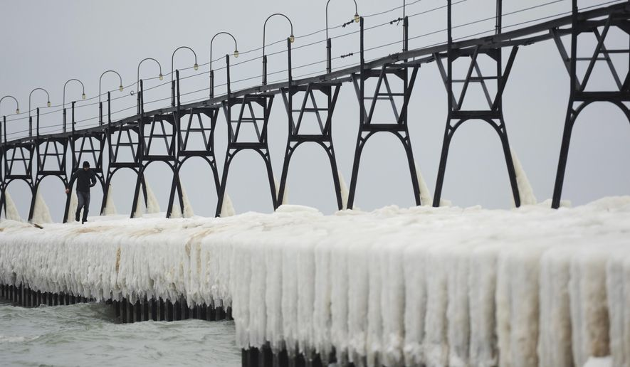 A man walks along the ice covered pier at the South Haven Lighthouse on Saturday, Dec. 24, 2016, in South Haven, Mich. (Don Campbell/The Herald-Palladium via AP)