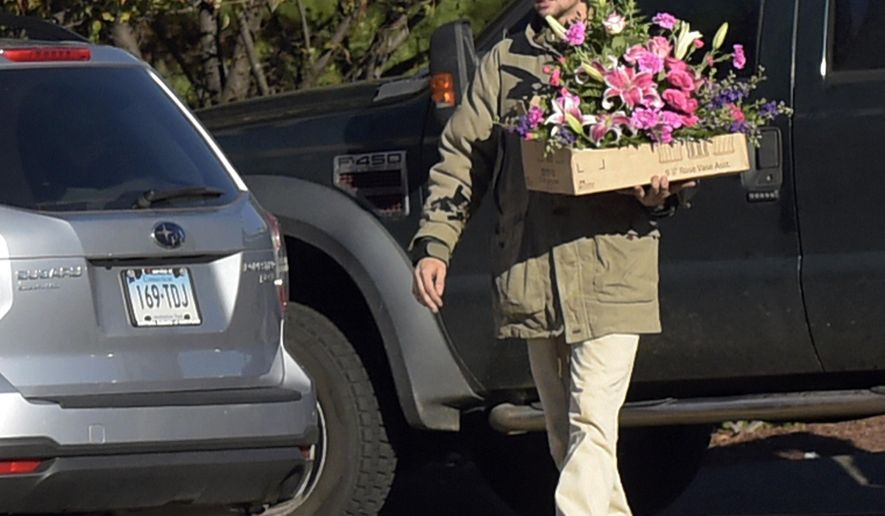 FILE - In this Oct. 26, 2016 file photo, Nathan Carman carries flowers to a memorial service for his mother Linda Carman, at Saint Patrick - Saint Anthony Church in Hartford, Conn. Nathan Carman spent a week at sea in a life raft before being rescued by a passing freighter. His mother who accompanied him on their ill-fated September fishing trip was missing and presumed dead. (Patrick Raycraft/The Hartford Courant via AP, File)