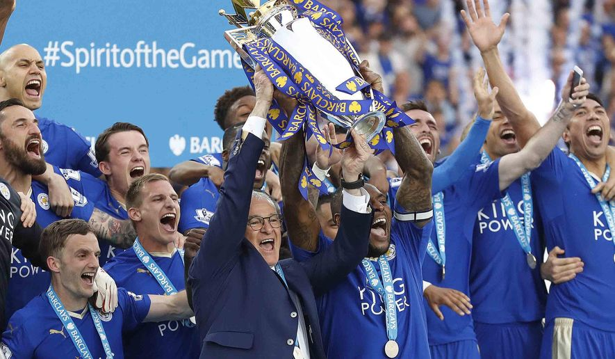 "FILE- In this May 7, 2016, file photo, Leicester's team manager Claudio Ranieri and Leicester's Wes Morgan lift the trophy as Leicester City celebrate becoming the English Premier League soccer champions at King Power stadium in Leicester, England. Leicester City, with a payroll that was spare change compared to the Premier League's big spenders, romped to the first league title in its 132-year history, clinching with two weeks to spare. ""Nobody believed we could do it,"" captain Morgan said, ""but here we are."" (AP Photo/Matt Dunham, File)"