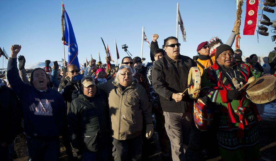 FILE - In this Dec. 4, 2016 file photo, protesters march at Oceti Sakowin camp where people have gathered to protest the Dakota Access oil pipeline in Cannon Ball, N.D. It has been called the largest gathering of Native American tribes in a century. Tribal members and others have joined in an ongoing, tense protest against the $3.8 billion Dakota Access oil pipeline, which the Standing Rock Sioux believes threatens sacred sites and a river that provides drinking water for millions of people. The protest is included in the AP top news stories in North Dakota this year. (AP Photo/David Goldman, File)