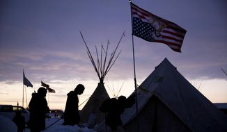 Travelers arrive at the Oceti Sakowin camp where people have gathered to protest the Dakota Access oil pipeline as they walk into a tent next to an upside-down american flag in Cannon Ball, N.D., in this Dec. 4, 2016, file photo. (AP Photo/David Goldman File)