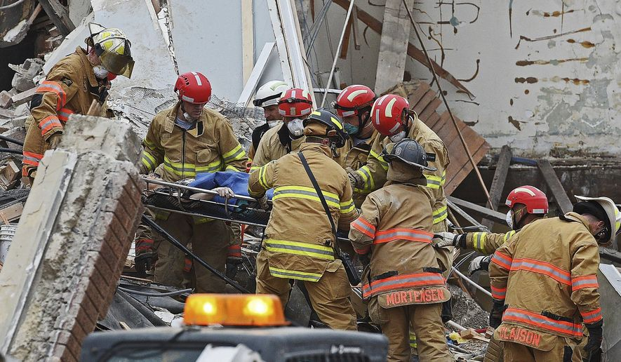 FILE - in this Dec. 2, 2016 file photo, a woman is rescued from the rubble by emergency personnel on scene after a building collapse in downtown Sioux Falls, S.D. The collapse of the 100-year old building that killed construction worker Ethan McMahon, a 24-year-old Marine, was included in the top AP news stories in South Dakota this year. (Joe Ahlquist  /The Argus Leader via AP, File)
