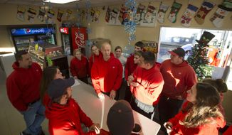 In this Dec. 12, 2016, photo, Bill Spencer, center, holds an impromptu staff meeting at the Union 76 gas station in Creswell, Ore., where many of the employees are high school and college students earning money for school. (Chris Pietsch/The Register-Guard via AP)