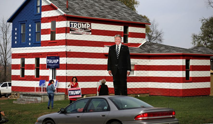 Lisa Rossi holds a campaign sign and waves at passing motorists outside her Donald Trump-themed House in Youngstown, Pennsylvania, on Election Day. (Associated Press)