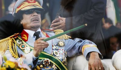 FILE - In this Tuesday, Sept. 1, 2009 file photo, Libyan leader Moammar Gadhafi gestures with a green cane as he takes his seat behind bulletproof glass for a military parade in Green Square, Tripoli, Libya. Gadhafi of nearly 42 years was captured by rebel forces in his hometown of Sirte in Oct. 2011. Libyan officials initially said Gadhafi was killed in crossfire between rebel fighters and loyalists. However, video footage emerged showing him being beaten, taunted and abused by his captors, raising questions about how and when he died. (AP Photo/Ben Curtis, File)