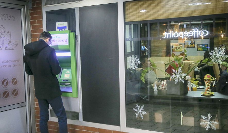 A client takes money from PrivatBank's cash machine as people enjoy in a city cafe in the centre Kiev, Ukraine, Monday, Dec. 19, 2016. Ukraine is nationalizing its largest bank PrivatBank following concerns over its stability. (AP Photo/Efrem Lukatsky)