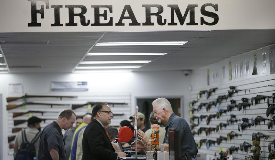 Sales associate Mike Conway (right) shows Paul Angulo guns at Bullseye Sport gun shop in Riverside, Calif., on Dec. 9, 2015. (Associated Press) **FILE**
