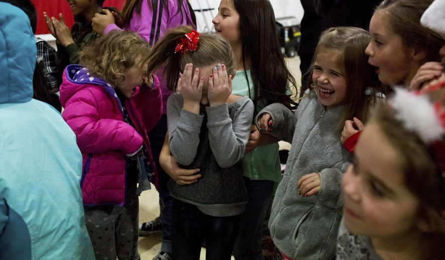 In this Dec. 21, 2016 photo, children react to the kiss after an engagement during a Christmas event at the Spanish Fork Airport in Spanish Fork, Utah. This year Santa brought toys for all the children as well as a very special gift for one couple. (Sammy Jo Hester/The Daily Herald via AP)