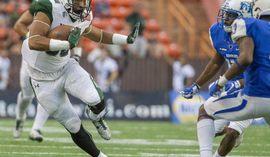 Hawaii wide receiver Ammon Barker, left, runs with the football for a first down after catching a pass on a fake-punt play against Middle Tennessee during the third quarter of the Hawaii Bowl NCAA college football game, Saturday, Dec. 24, 2016, in Honolulu. (AP Photo/Eugene Tanner)