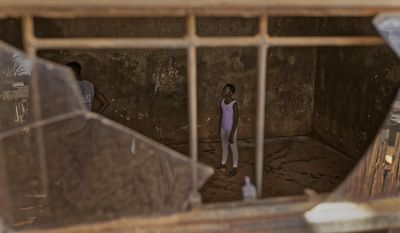 In this photo taken Friday, Dec. 9, 2016, a young ballerina waits for Kenyan ballet dancer Joel Kioko, 16, left, to teach a class in a room at a school in the Kibera slum of Nairobi, Kenya. In a country not usually associated with classical ballet, Kenya's most promising young ballet dancer Joel Kioko has come home for Christmas from his training in the United States, to dance a solo in The Nutcracker and teach holiday classes to aspiring dancers in Kibera, the Kenyan capital's largest slum. (AP Photo/Ben Curtis)