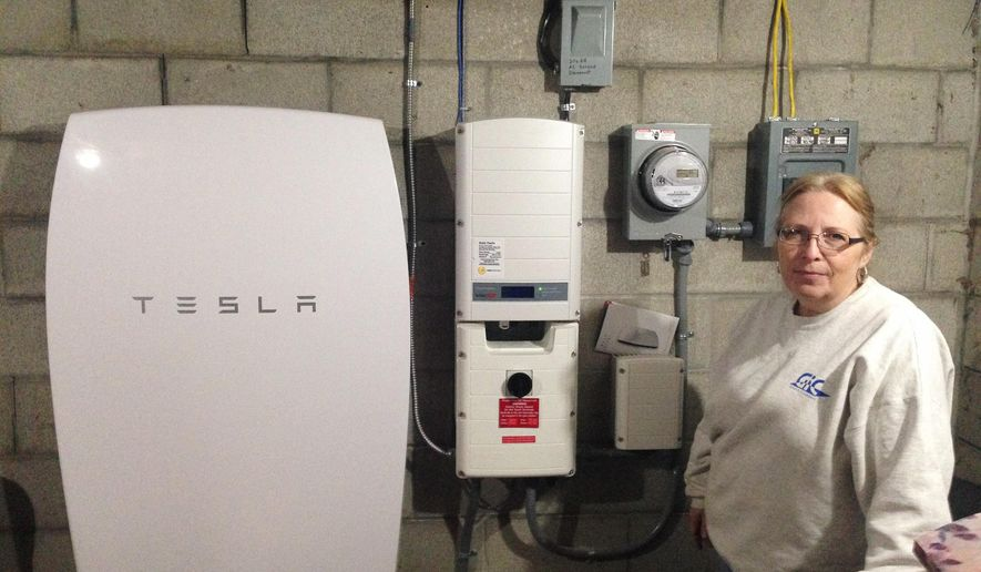 "In this Oct. 27, 2016 photo, Rhonda ""Honey"" Phillips poses next to a Tesla Powerwall battery and inverter connected to a solar panel array in her yard in Middletown Springs, Vt. Phillips is one of the growing number of Green Mountain Power customers using the Tesla battery to store solar energy when her panels aren't collecting it. GMP has been working to link solar energy with battery storage on both a large and small scale. (AP Photo/Dave Gram)"