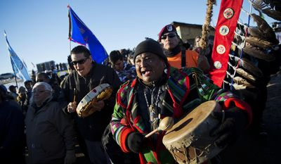 FILE - In this Dec 4, 2016, file photo, Dan Nanamkin, of the Colville Nez Perce Native American tribe in Nespelem, Wash., right, drums with a procession through the Oceti Sakowin camp after it was announced that the U.S. Army Corps of Engineers won't grant easement for the Dakota Access oil pipeline in Cannon Ball, N.D. Some Native Americans worry the transition to a Donald Trump administration signals an end to eight years of sweeping Indian Country policy reforms. Trump rarely acknowledged Native Americans during his campaign. And he hasn't publicly outlined since the election how he would improve or manage the United States' longstanding relationships with tribes. But Trump's Native American supporters said they're hopeful he will cut through some of the government red tape that they believe has stifled economic progress on reservations. (AP Photo/David Goldman, File)