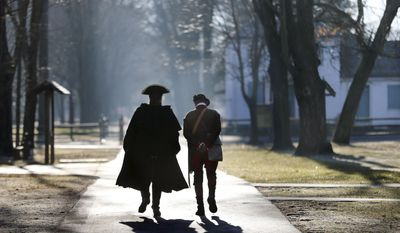 Revolutionary War re-enactors walk along a path before the re-enactment of Gen. George Washington's Christmas Day crossing to New Jersey on Sunday, Dec. 25, 2016, in Washington Crossing, Pa. (AP Photo/Mel Evans)