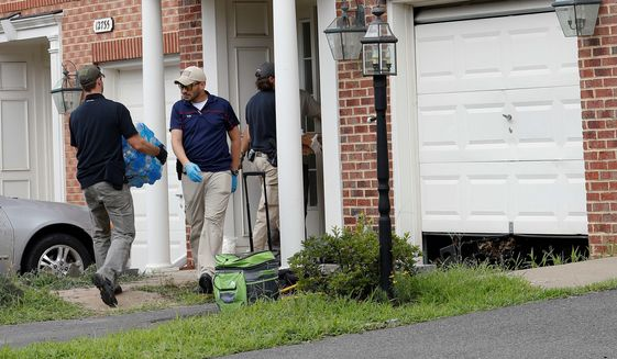 Law enforcement officers work outside the home of Nicholas Young on Aug. 3, 2016, in Fairfax, Virginia. Young, who worked as a Metro police officer, has been charged with helping the Islamic State. (Associated Press)
