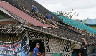 Residents fix the roof of their house after it was blown off by typhoon Nock-Ten, a day after Christmas Monday, Dec. 26, 2016 at Mabini township, Batangas province south of Manila, Philippines. The powerful typhoon slammed into the eastern Philippines on Christmas Day, spoiling the biggest holiday in Asia's largest Catholic nation but weakened slightly on Monday as it roared toward a congested region near the country's capital, officials said. (AP Photo/Bullit Marquez)