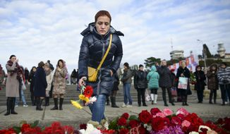 A woman puts flowers at a pier in Sochi, Russia, Monday, Dec. 26, 2016. All 84 passengers and eight crew members on the Russian military's Tu-154 plane are believed to have died Sunday morning when it crashed two minutes after taking off from the southern Russian city of Sochi. (AP Photo/Viktor Klyushin)