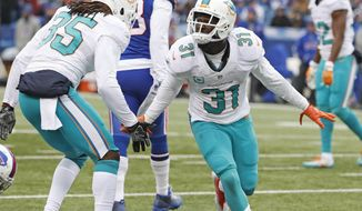 Miami Dolphins free safety Michael Thomas (31) and safety Walt Aikens (35) celebrate a defensive play in the first half of an NFL football game against the Buffalo Bills in Orchard Park, N.Y., Saturday, Dec. 24, 2016. (Al Diaz/Miami Herald via AP)