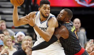 Minnesota Timberwolves' Karl-Anthony Towns, left, keeps the ball at bay from Atlanta Hawks' Paul Millsap during the first half of an NBA basketball game Monday, Dec. 26, 2016, in Minneapolis. (AP Photo/Jim Mone)