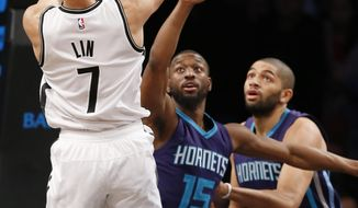 Charlotte Hornets' guard Kemba Walker (15) and Hornets' guard Nicolas Batum (5) defend Brooklyn Nets guard Jeremy Lin (7) who shoots in the first half of an NBA basketball game, Monday, Dec. 26, 2016, in New York. (AP Photo/Kathy Willens)